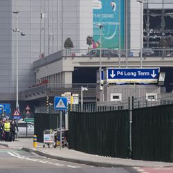Airline staff, left, leaves Zaventem airport under escort as the blown out windows are seen top right in Brussels, Belgium, Tuesday, March 22, 2016. Authorities in Europe have tightened security at airports, on subways, at the borders and on city streets after deadly attacks Tuesday on the Brussels airport and its subway system.