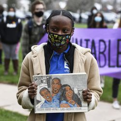 Denver South High School student, Graça Jovelino, 16, a recent immigrant from Angola, holds her drawing of Ahmaud Arbery, left, George Floyd, center, and Breonna Taylor. right, during a 9 minute and 29 second moment of silence at Denver South High School on April 21, 2021.