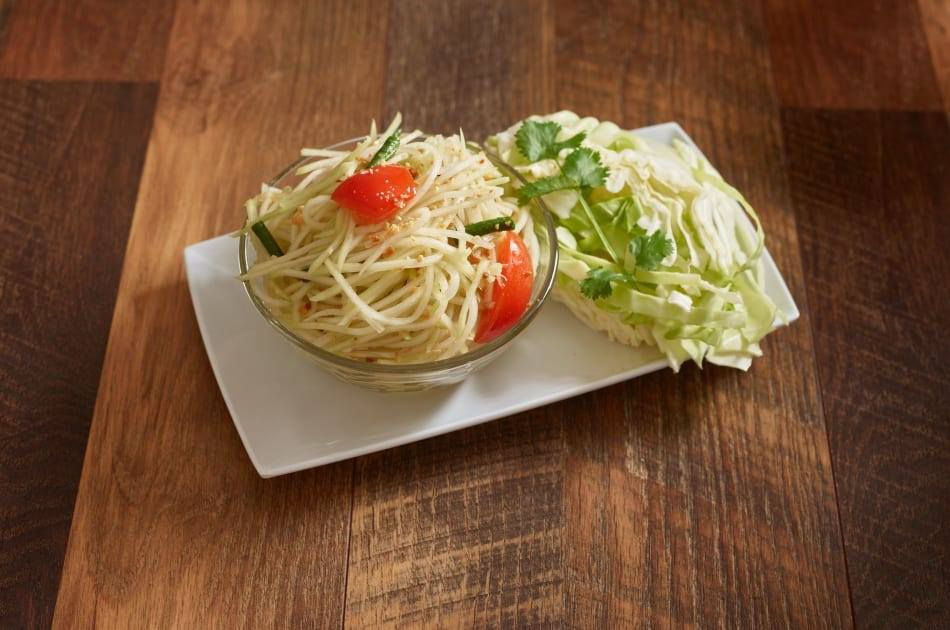 A wooden table holds a white plate with fresh papaya salad on top.