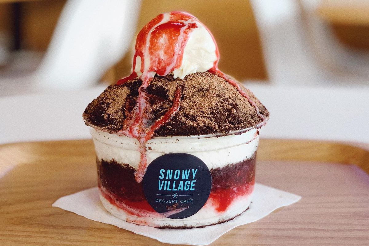 A cup of shaved ice with red syrup drizzled over it at Snowy Village in the University District