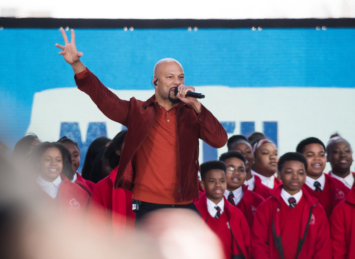 Hip-hop artist Common performs onstage backed by students in their school uniforms at the March for Our Lives in Washington, D.C.