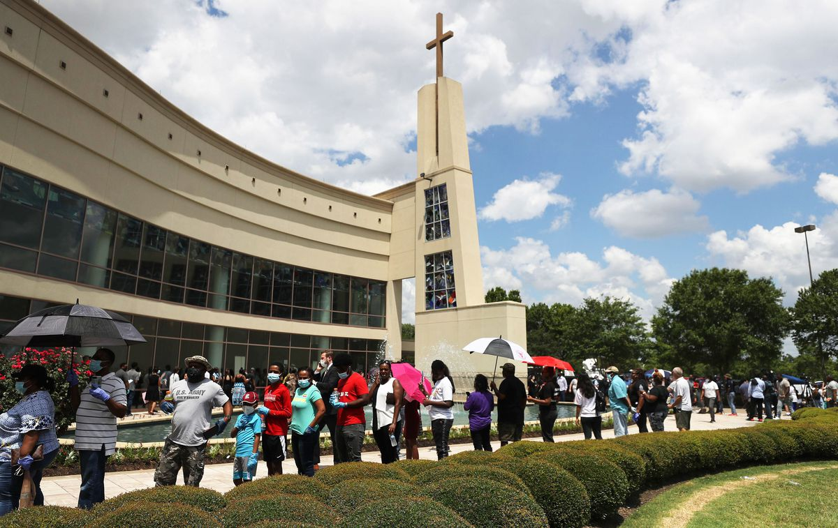 People wait in line Monday to attend the public memorial for George Floyd outside the Fountain of Praise church in Houston.