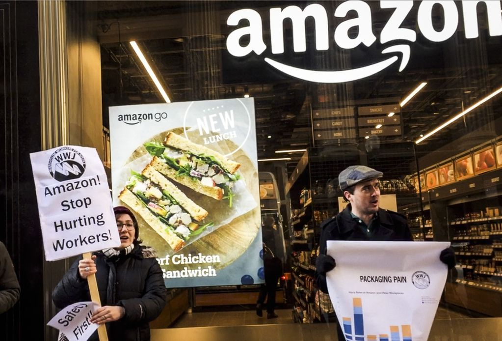 Amazon workers and community activists demonstrate outside a downtown Amazon Go store Tuesday.