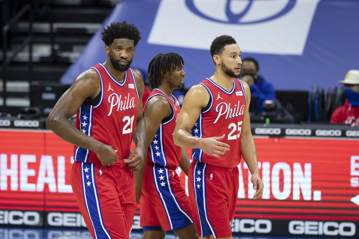 Joel Embiid, Tyrese Maxey, and Ben Simmons of the Philadelphia 76ers look on against the Miami Heat at the Wells Fargo Center on January 14, 2021 in Philadelphia, Pennsylvania.