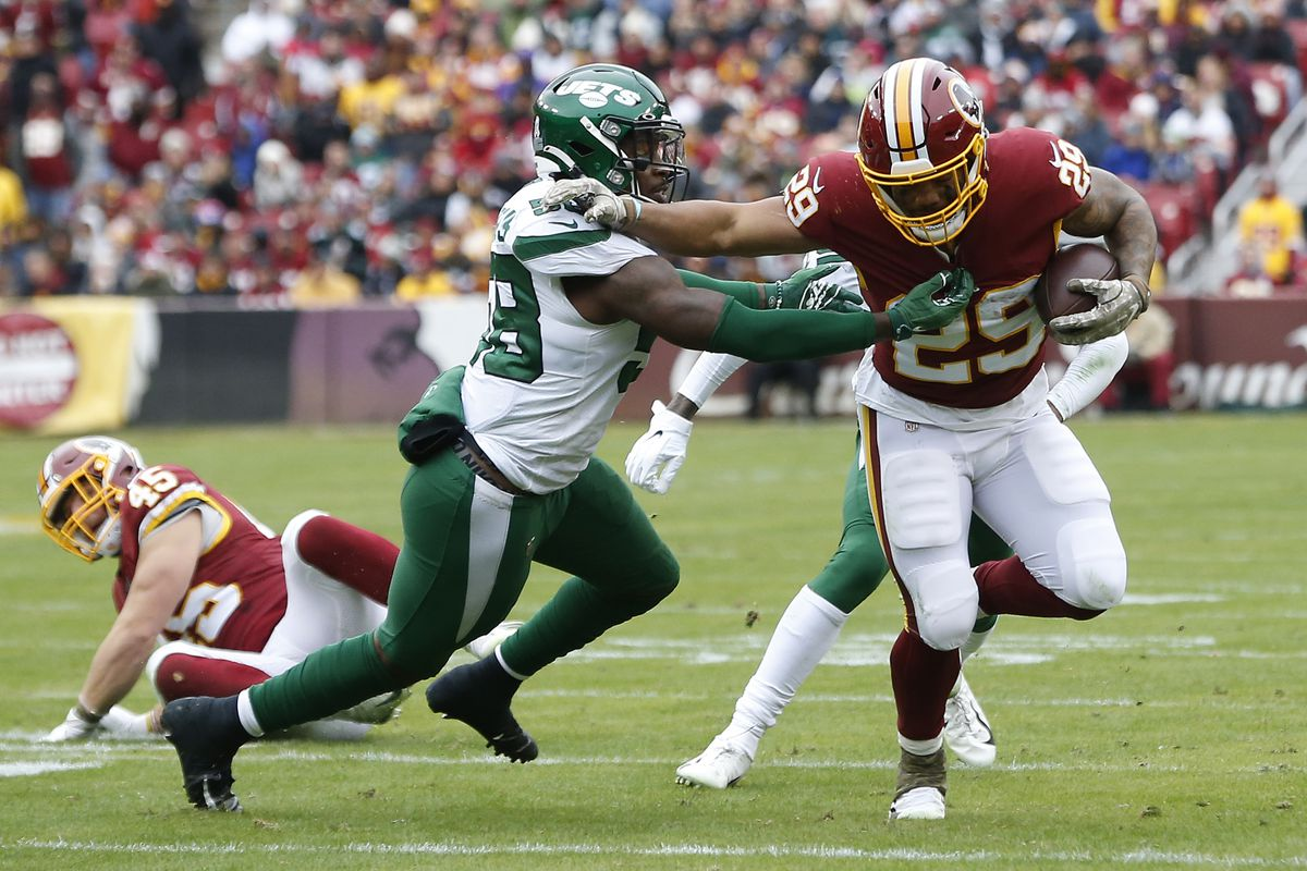 Washington running back Derrius Guice carries the ball as New York Jets outside linebacker James Burgess defends in the second quarter at FedExField.