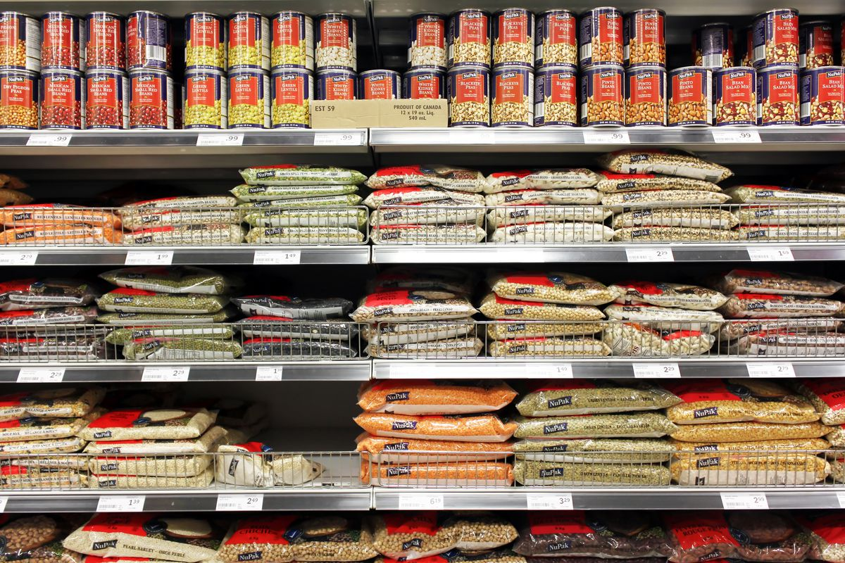 Grocery store shelf filled with dried and canned beans.
