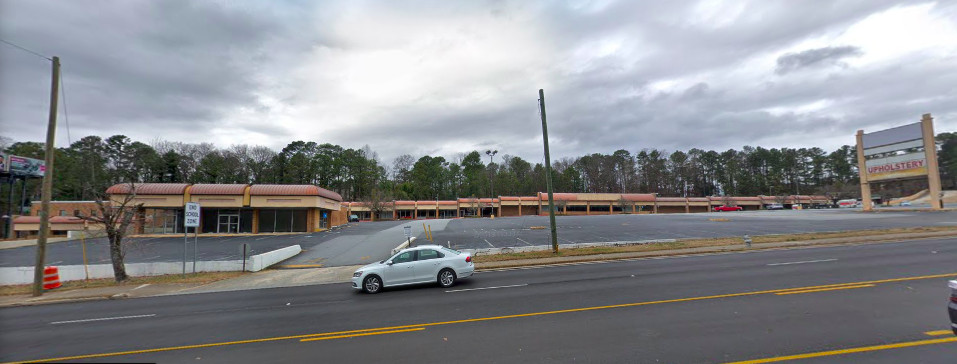 A huge empty shopping center with a big parking lot in front.