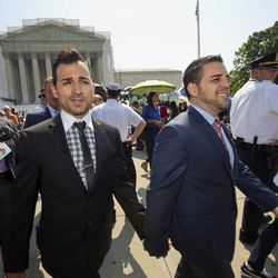 Proposition 8 case plaintiffs, Jeff Zarrillo, center, holds hands with his partner Paul Katami, right, as they leave the Supreme Court in Washington, Tuesday, June 25, 2013, without a decision in Hollingsworth v. Perry, California Proposition 8 case. At far left is plaintiff Kris Perry.   (AP Photo/J. Scott Applewhite)