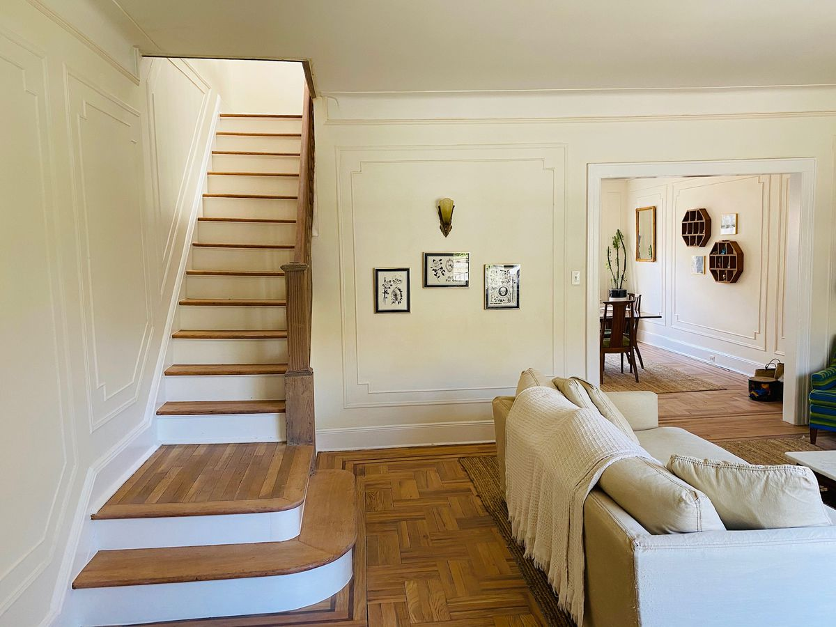 A wooden staircase next to the living room.