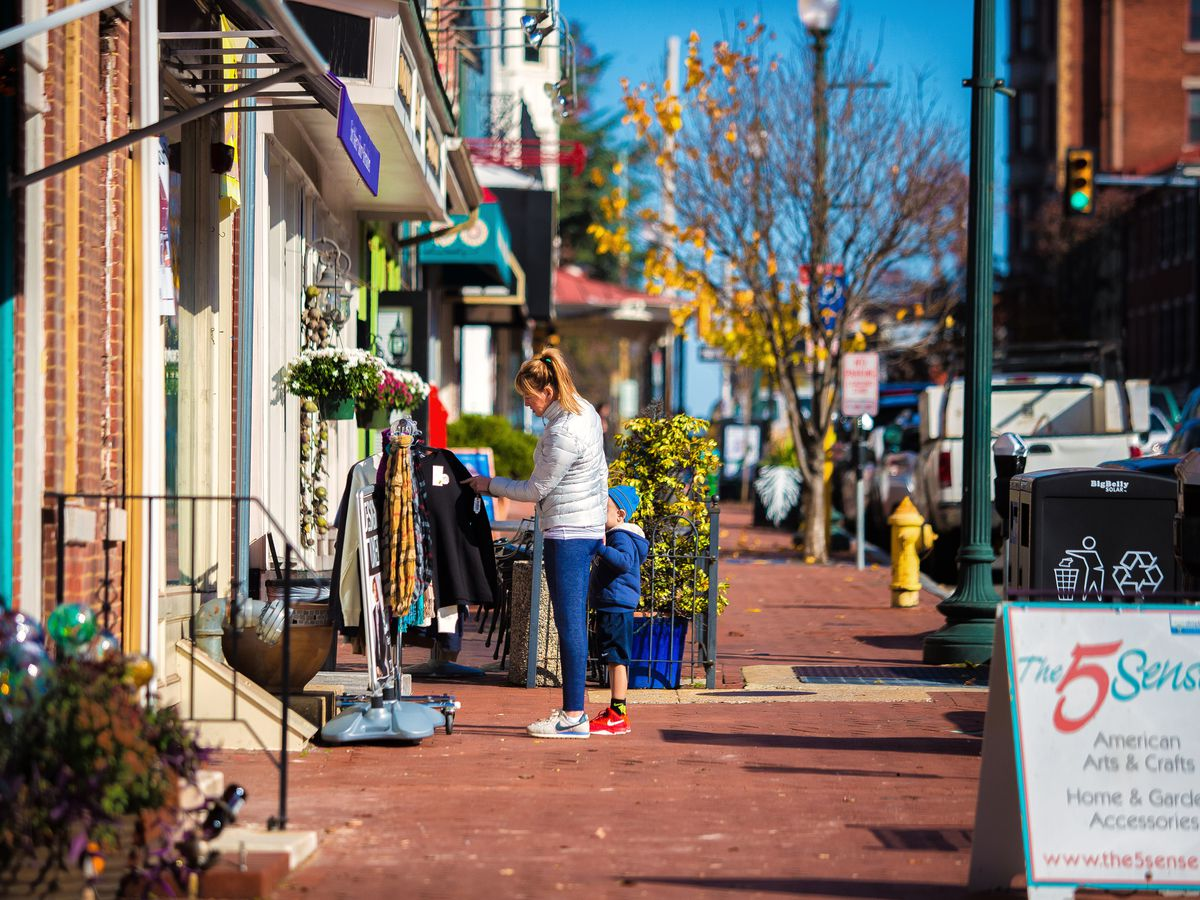 A sidewalk in the town of West Chester, Pennsylvania. The sidewalk is red brick and there are shops and trees.
