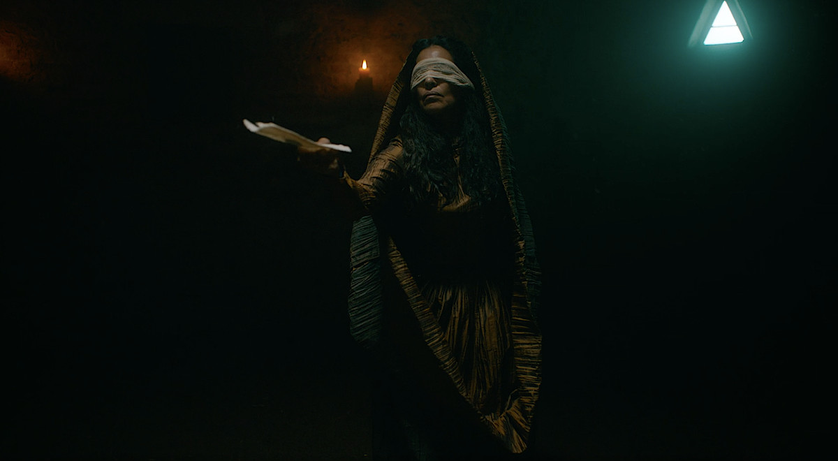 Sarita Choudhury, blindfolded and in long, dark-colored robes, extends a folded letter in the air in The Green Knight