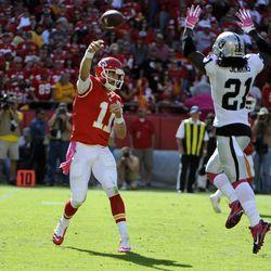 Kansas City Chiefs quarterback Alex Smith (11) throws a pass against Oakland Raiders cornerback Mike Jenkins (21) in the second half at Arrowhead Stadium. Kansas City won the game 24-7.