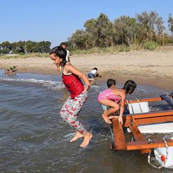 Children play at the beach at Kyllini refugee camp in Myrsini, Greece, July 11, 2016. The camp was previously a luxury resort before it fell into disrepair and was later turned into a refugee camp.