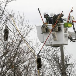 Utility workers repair power lines at the scene of a collision involving eight vehicles spanning the block between 300 East and 400 East on 400 North in Bountiful on Thursday, Dec. 10, 2020. A dump truck hit a power pole and seven vehicles, some vacant and parked, leaving four people injured.