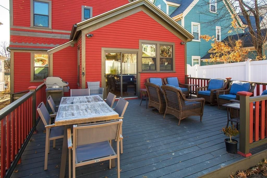 A spacious deck behind a house with furniture.
