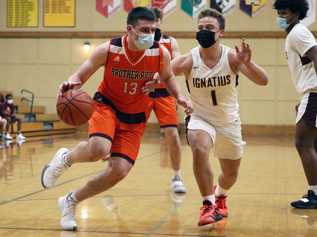 Brother Rice's Cullen Cosme (13) drives toward the basket as St. Ignatius' Parker Higginbottom (1) defends.