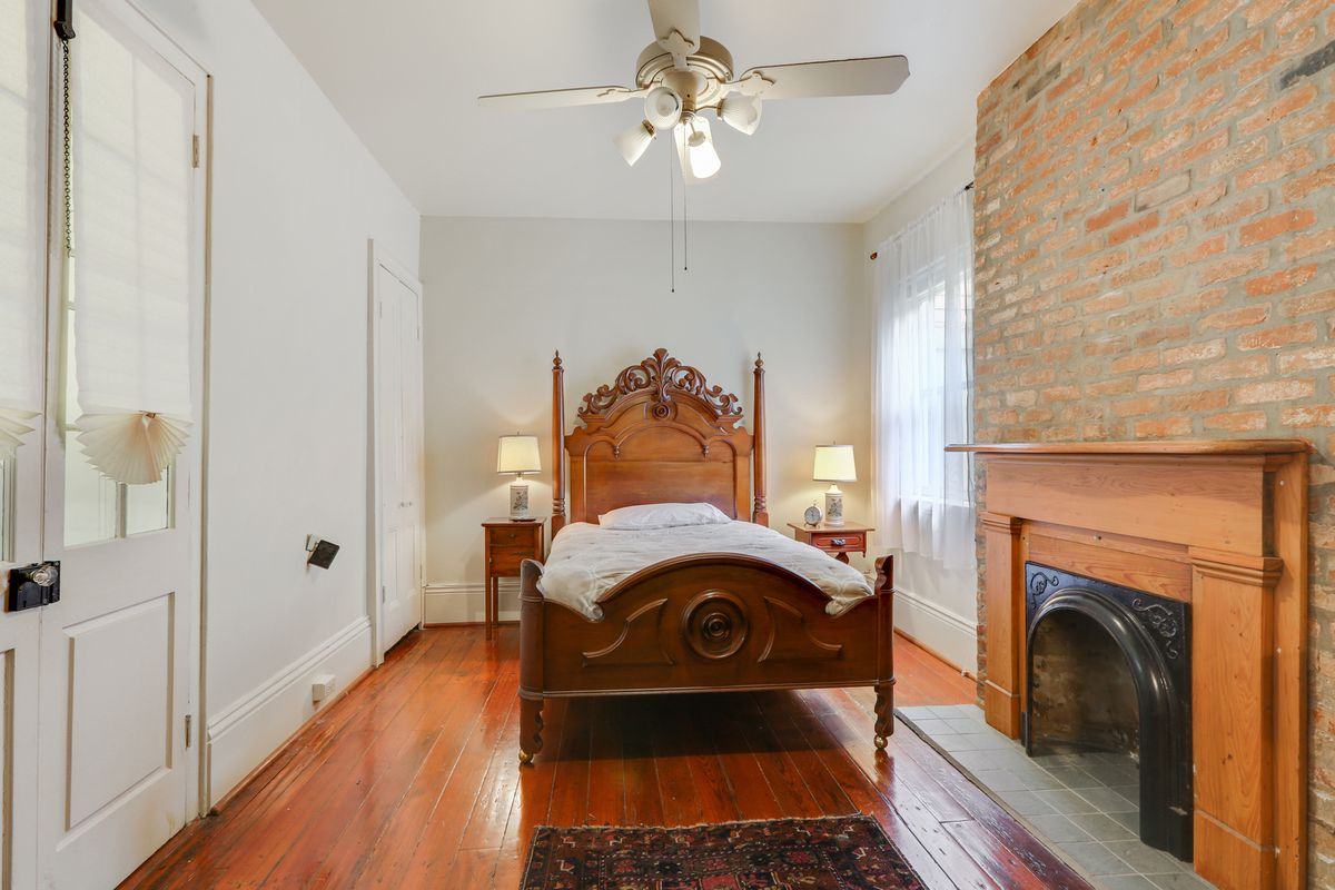 A bedroom with an old-fashioned poster bed, brick fireplace, white walls and wood floors.