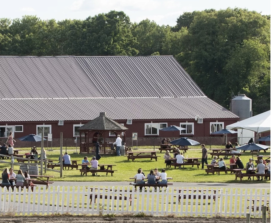 tables under umbrellas are outside a barn structure, several feet apart.
