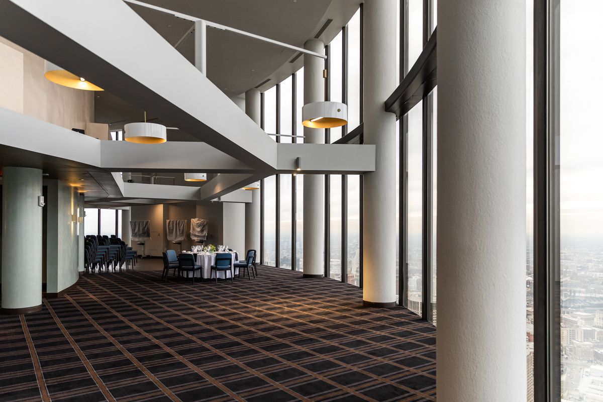 A carpeted room with one table set up at the back and white concrete columns along windows overlooking downtown Detroit.