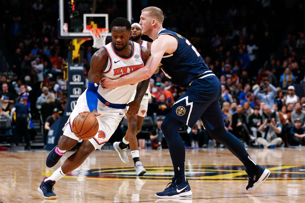 New York Knicks forward Julius Randle is fouled by Denver Nuggets forward Mason Plumlee in the fourth quarter at the Pepsi Center.