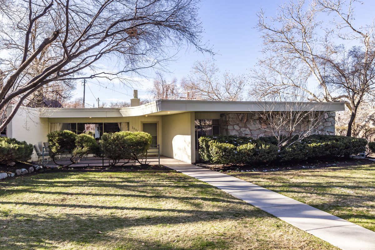 An exterior view of a ranch-style house with stone walls, a thick flat roofline, and grass with a sidewalk leading to the house.