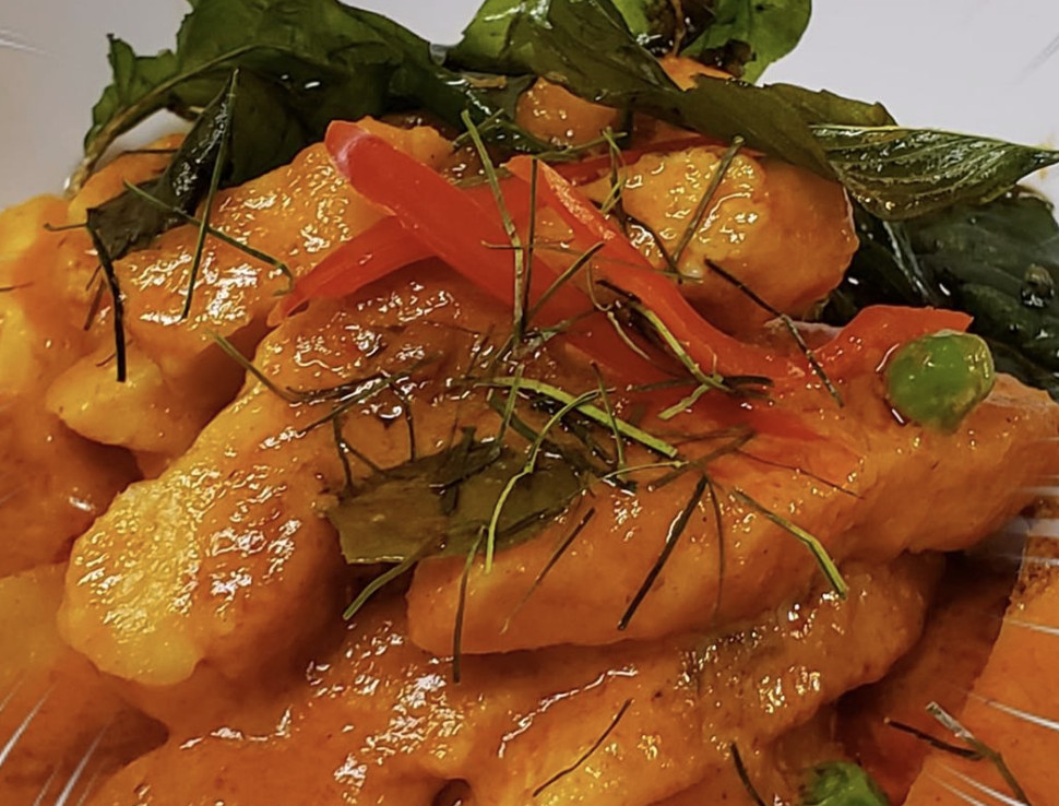 A closeup of grilled chicken with Panang curry sauce topped with basil and dill leaves