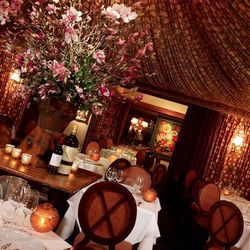 Damaged by a kitchen fire in 2001, a $4 million dollar renovation gutted the Fleur de Lys space before recreating it as a burgundy print-drenched dining room with an intimate cloth tent ceiling, Venetian chandelier, tall flower arrangement, and ornate wal