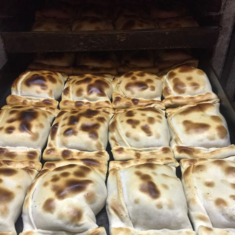 A tray of well-stuffed, square empanadas emerges from the oven singed heavily all over