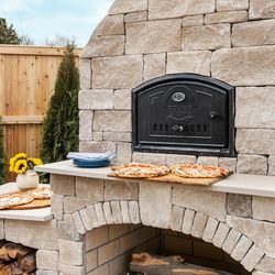 The outdoor kitchen, gas fireplace, and wood-fired pizza oven, built with steel framing and magnesium oxide cement board, were trucked to the site in pieces from Ohio, assembled, then faced with natural limestone. <em>Pizza oven: </em><a class=