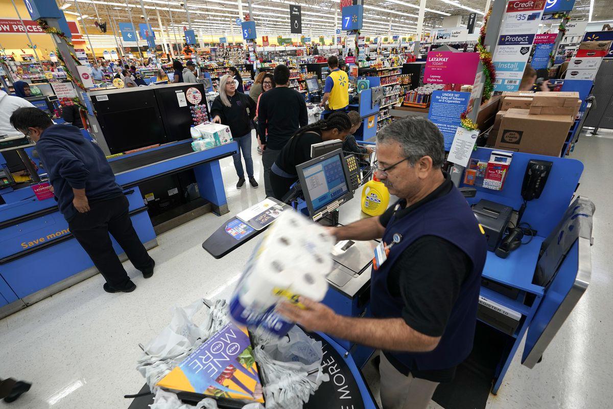 FILE- In this Nov. 9, 2018, file photo Walmart associate Javaid Vohar, right, checks out customers at a Walmart Supercenter in Houston. Walmart Inc. reports earnings Thursday, Nov. 15. (AP Photo/David J. Phillip, File)