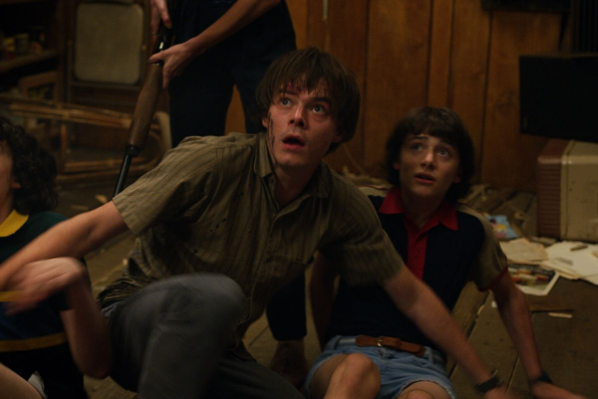 A scene from the third season of Netflix's Stranger Things showing once young man shielding another from an unseen threat.