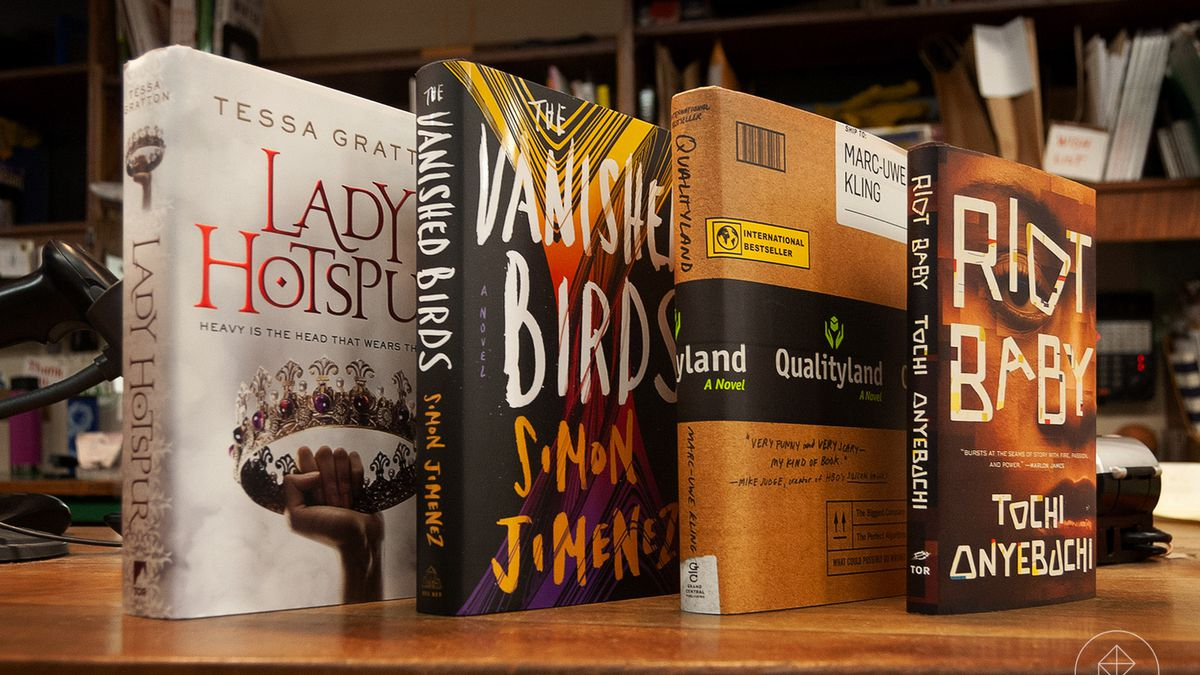Four books stood upright on a a book store counter