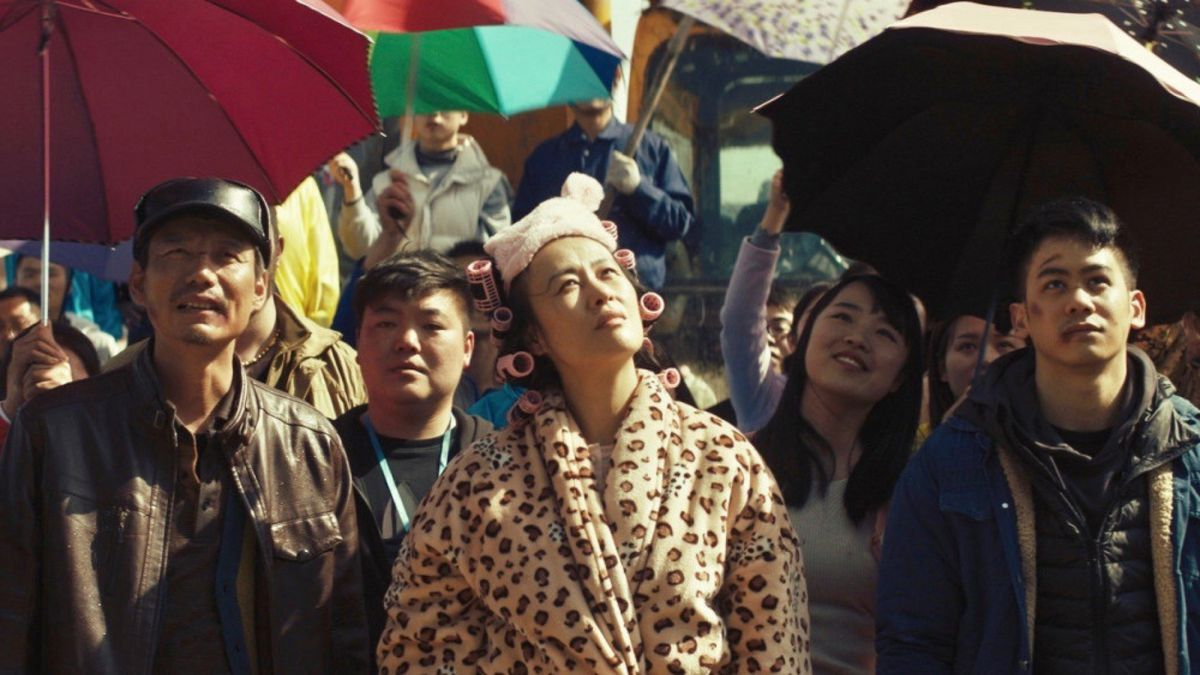 Dead Pigs: a woman in hair curlers and a leopard print coat looks around with other people holding umbrellas behind her