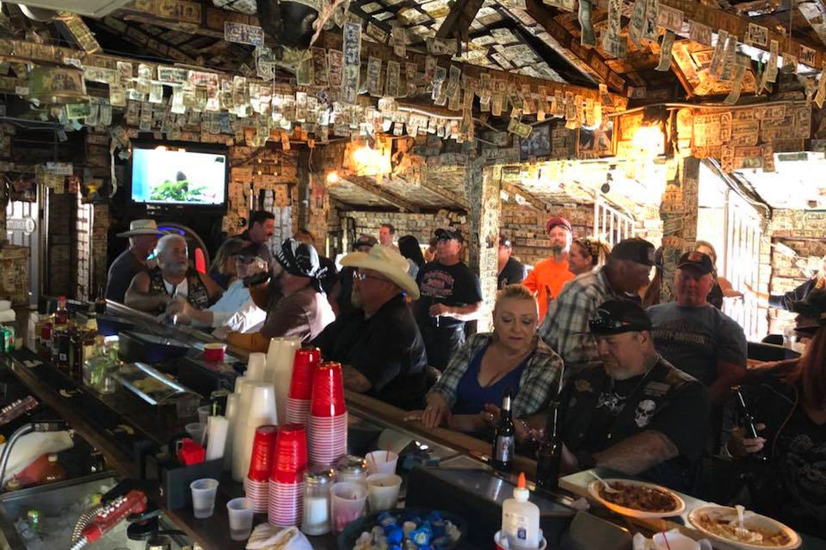 The interior of the Mountain Springs Saloon, decorated with inscribed dollar bills and busy with with visiting biker customers.