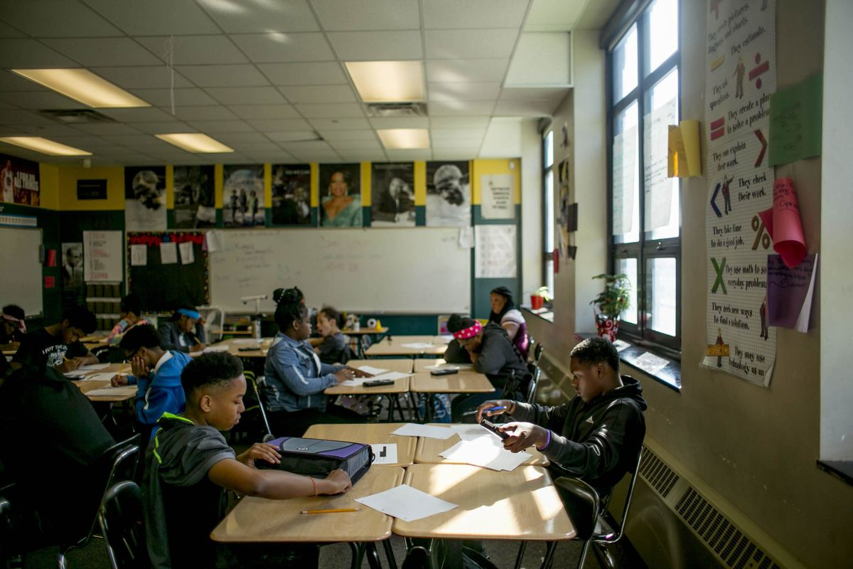 Several high school students work independently at their desks in a classroom.