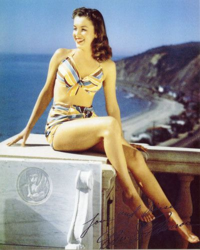 Young Marilyn Monroe with wavy brown hair perched on a ledge over Pacific Coast Highway, with the ocean and cliffs in the background. She's wearing a blue, yellow, and brown striped bikini.
