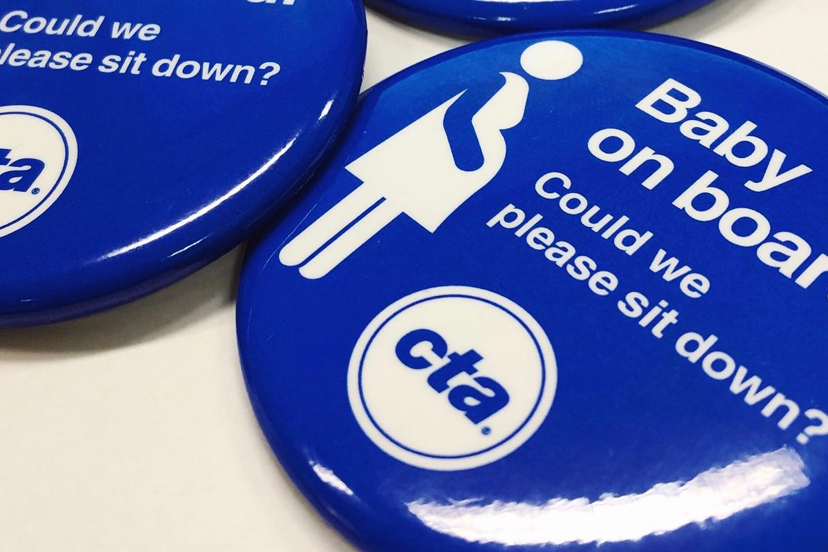 """A close-up photos shows part of a blue pin with white text that says """"Baby on board. Could we please sit down?"""" with a CTA logo and stick figure of a pregnant woman."""