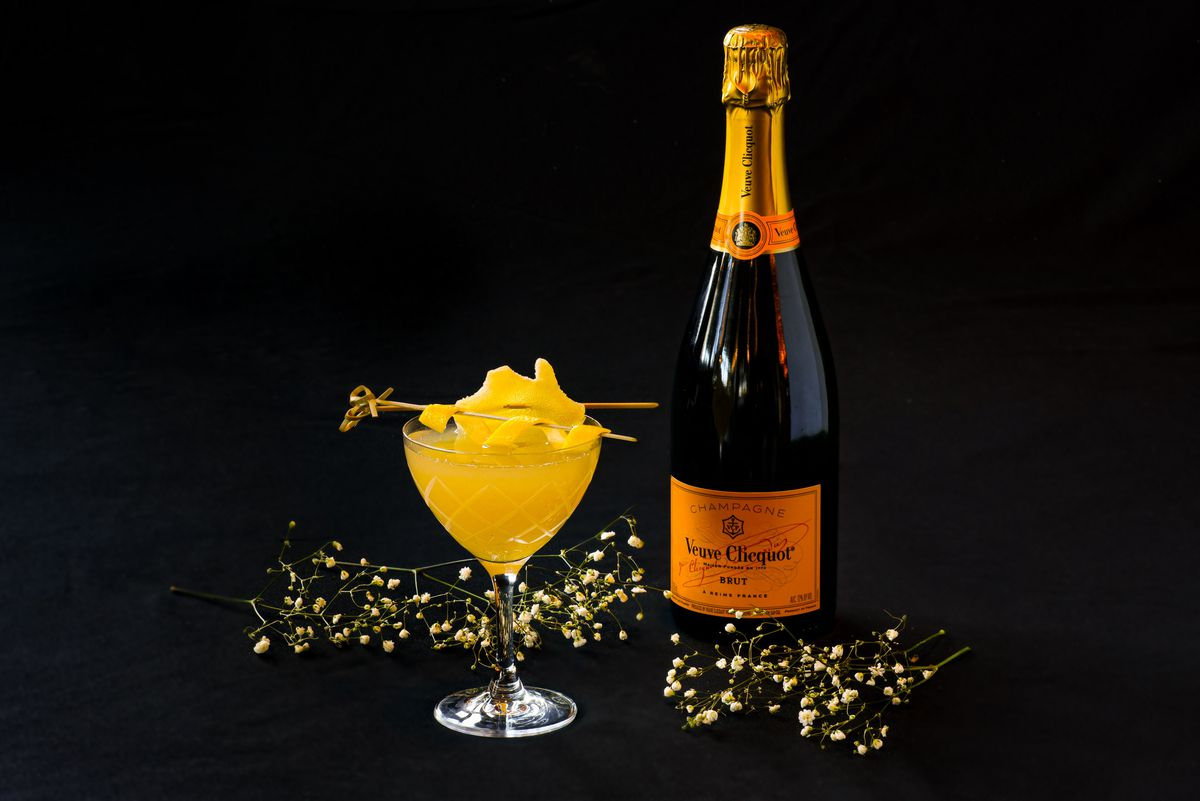 A bottle of Champagne and an orange cocktail
