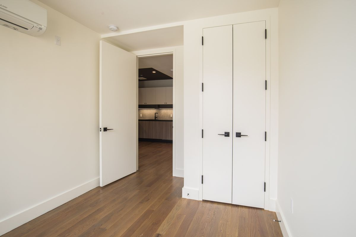 A room with beige walls, hardwood floors, and a small closet.