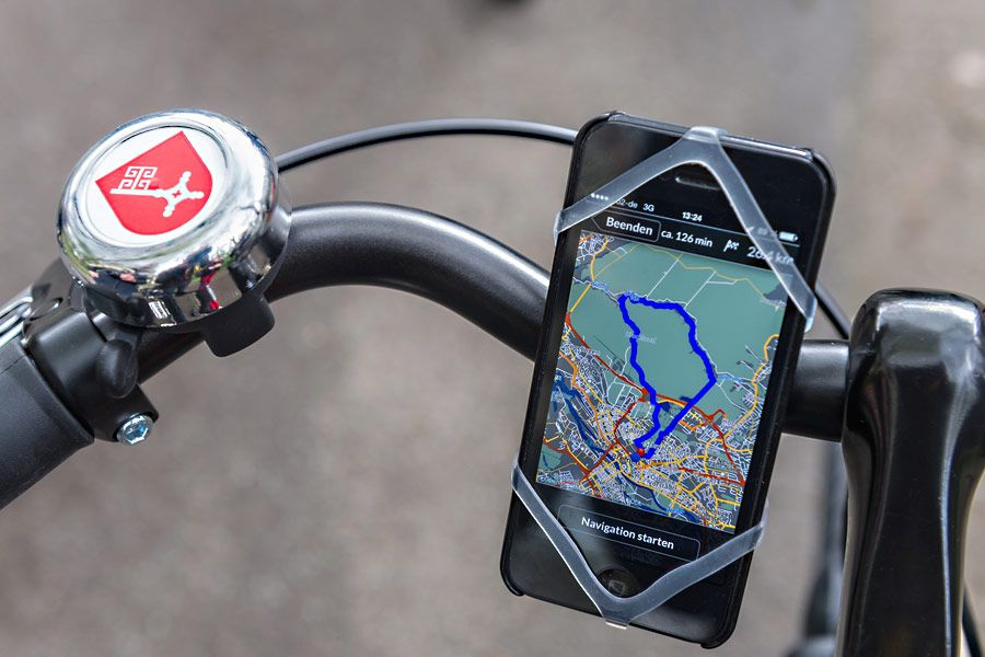 The handlebars of a bicycle. Attached to the handlebars in a holder is a mobile phone. On the mobile phone screen is a map.