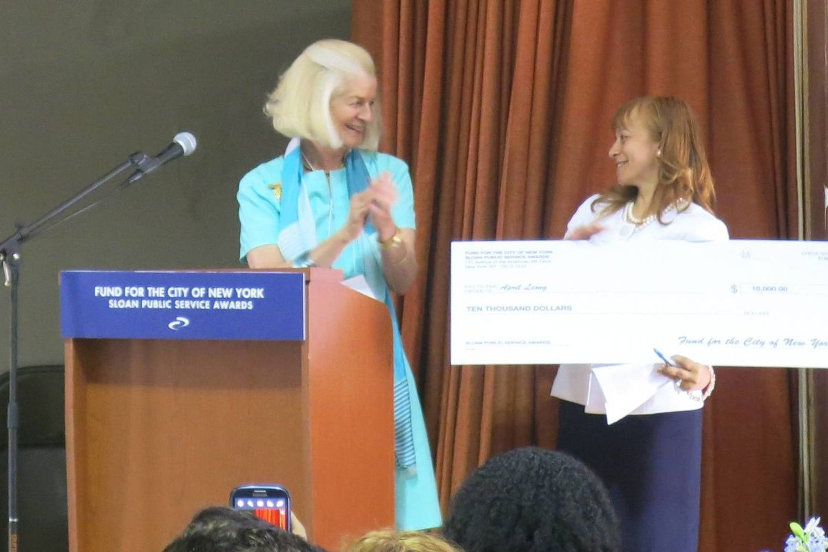Liberation Diploma Plus High School Principal April Leong (right) receives her $10,000 check as a recipient of the 2014 Sloan Public Service Awards.
