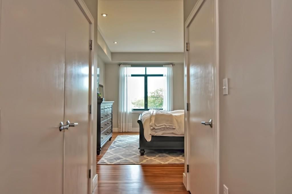 A narrow hallway leading to a bedroom, and the end of the bed is visible.