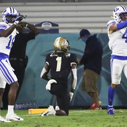 Brigham Young Cougars defensive back D'Angelo Mandell (16) and Brigham Young Cougars defensive back Troy Warner (4) applaud after UCF Knights wide receiver Jaylon Robinson (1) dropped the ball on a sure touchdown during the Boca Raton Bowl in Boca Raton, Fla., on Tuesday, Dec. 22, 2020.