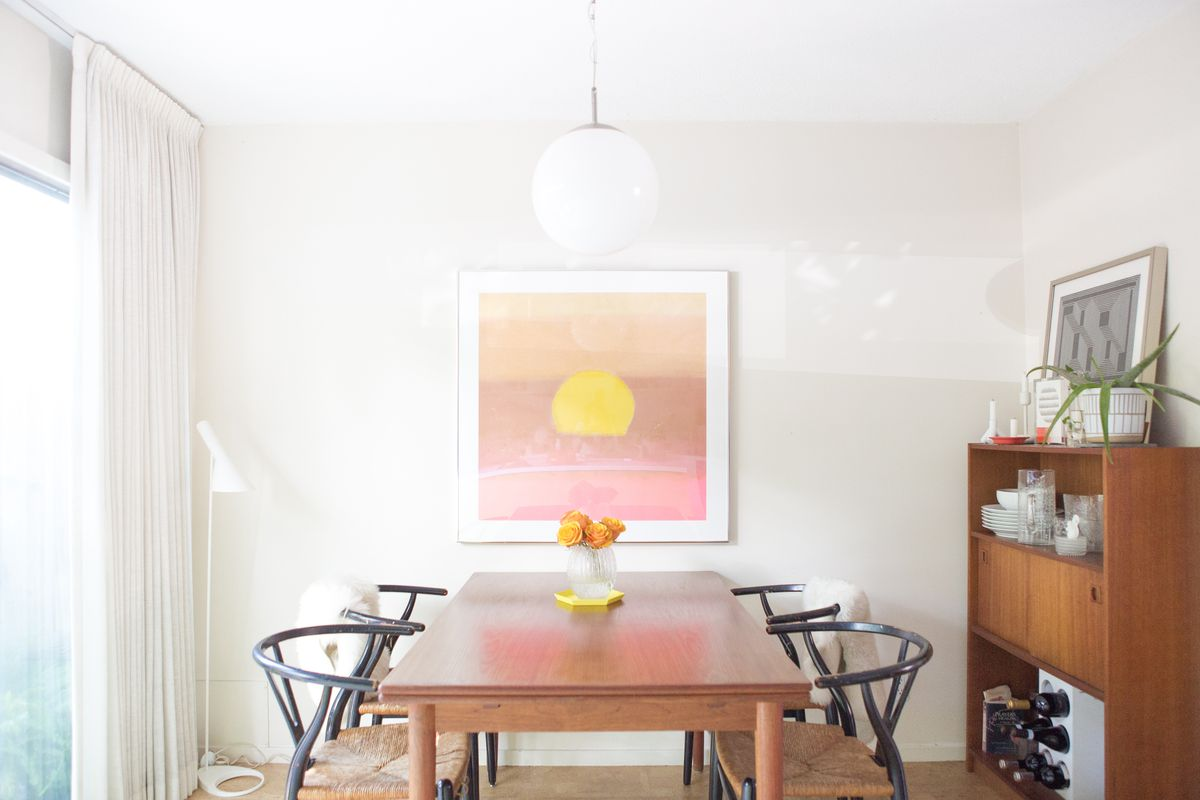 A bright dining table with wooden dining table, wishbone chairs, and a pink and yellow print in the background. A white orb light hangs from the ceiling.