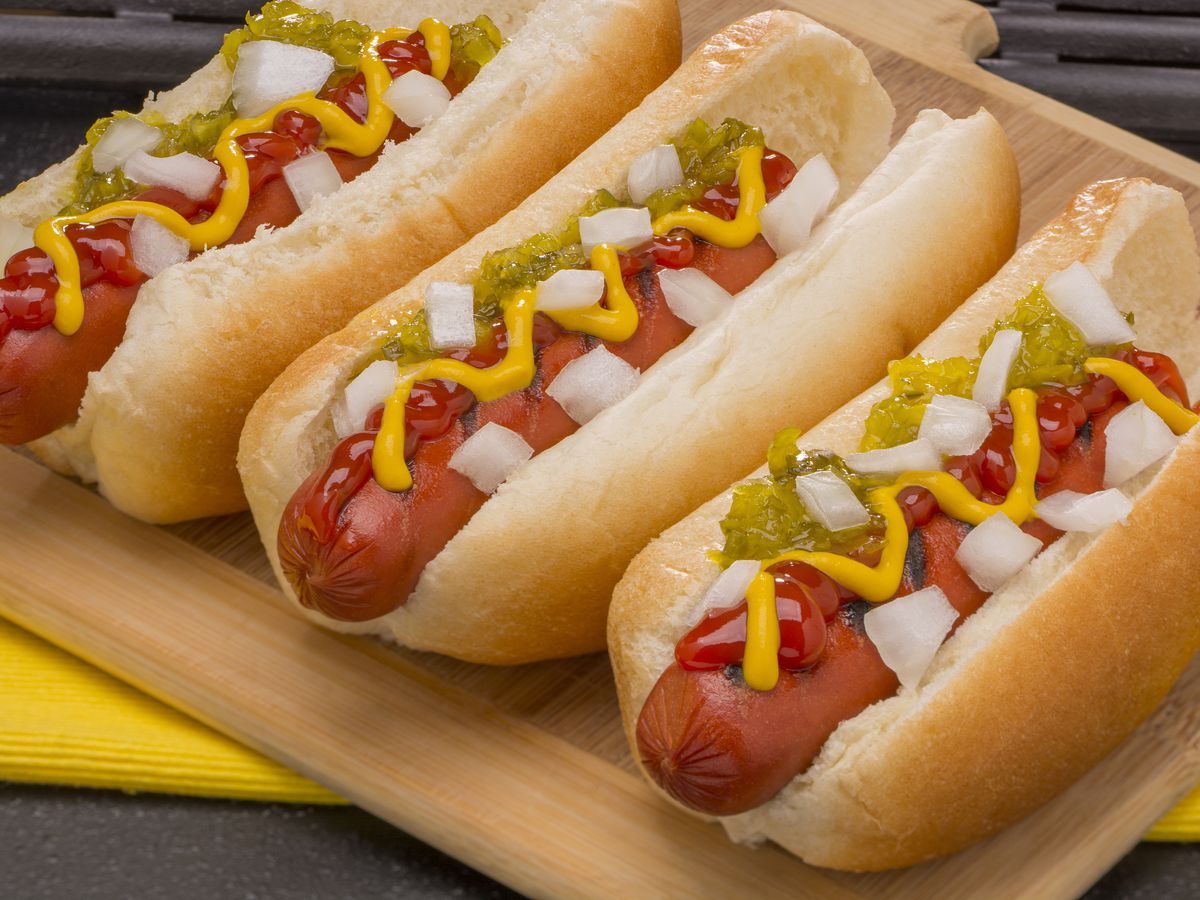 A close up image of three hot dogs topped with relish, onion and mustard