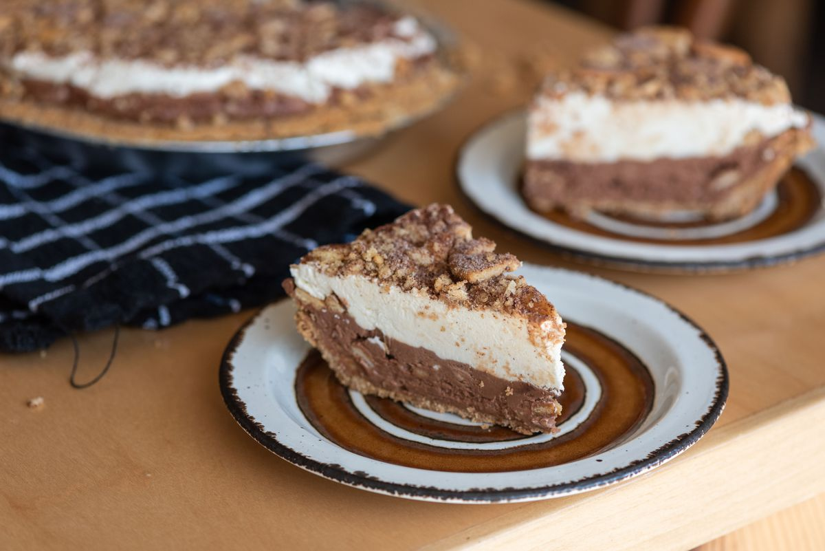 A slice of a two-layer cream pie on a plate.