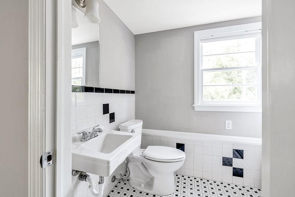 A white-tiled small bathroom with a window.