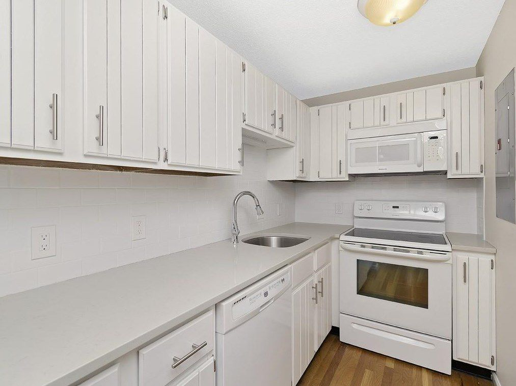 A small kitchen with a counter leading to a stove.
