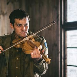 """Jack Ashton acts as Clair Cline playing a violin he made as a prisoner of war in northern Germany during World War II, as illustrated in """"Instrument of War."""""""