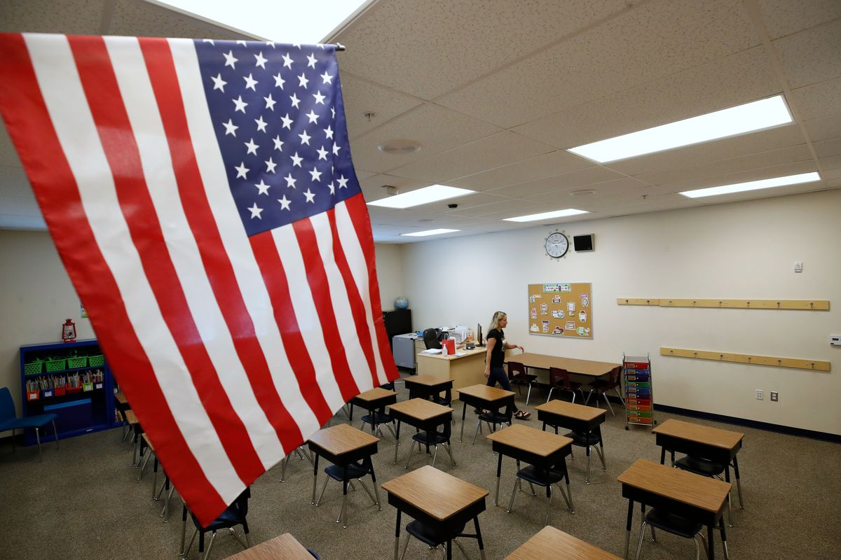 An empty schoolroom with a US flag.